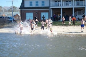 college students running into a river from a sandy beach