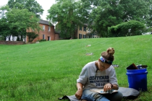 female student sitting outside on the grass reading a book
