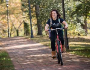 Student riding bike on brick path
