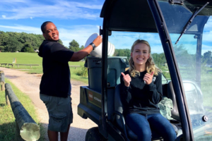Two compost volunteers riding in vehicle