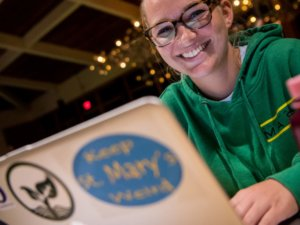 girl with cool sustainability stickers on laptop