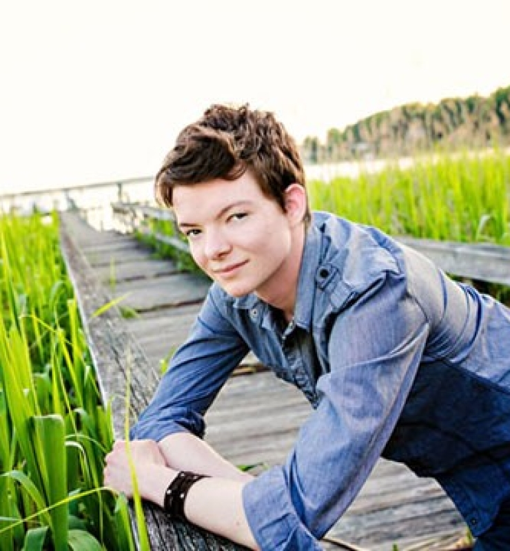 Griffyn Gilligan poses on a bridge over a marsh.