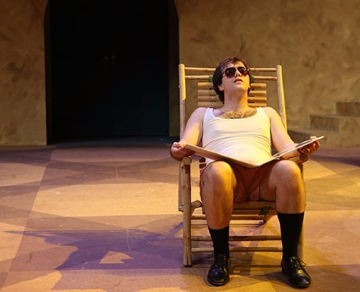 """Joe sits alone in a chair with a book in """"Much Ado""""."""
