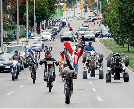The 12 o'Clock Boys on motorbikes drive down a busy highway.