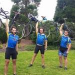 Three guys lifting bikes into the air