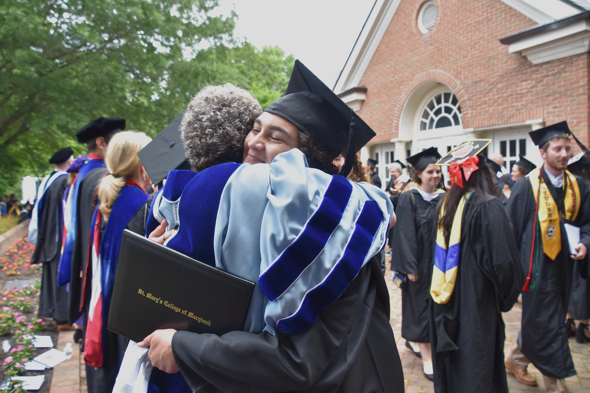 New graduates and faculty hugging it out at Commencement