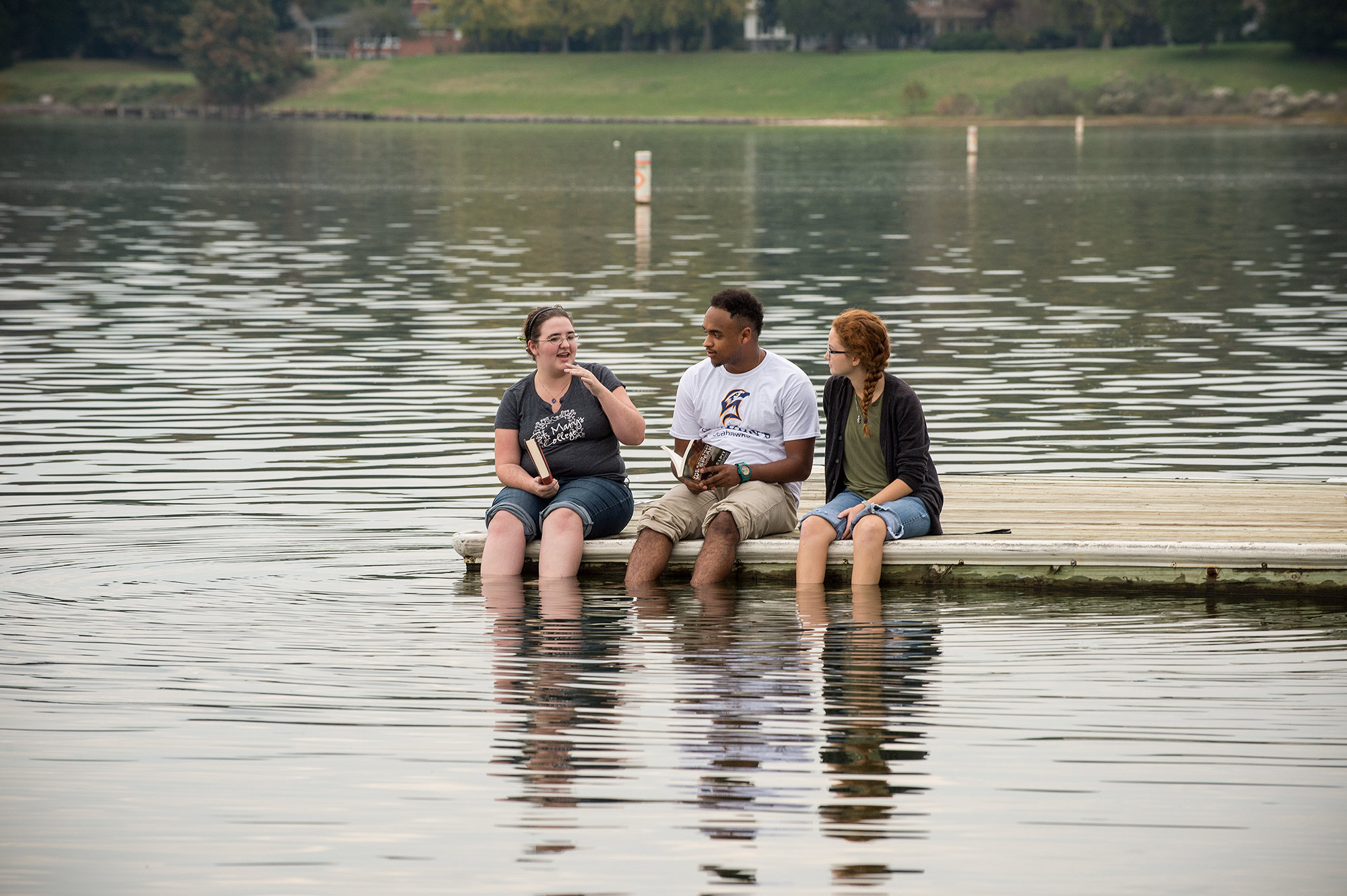 Three students sitting on a dock discussing their readings.