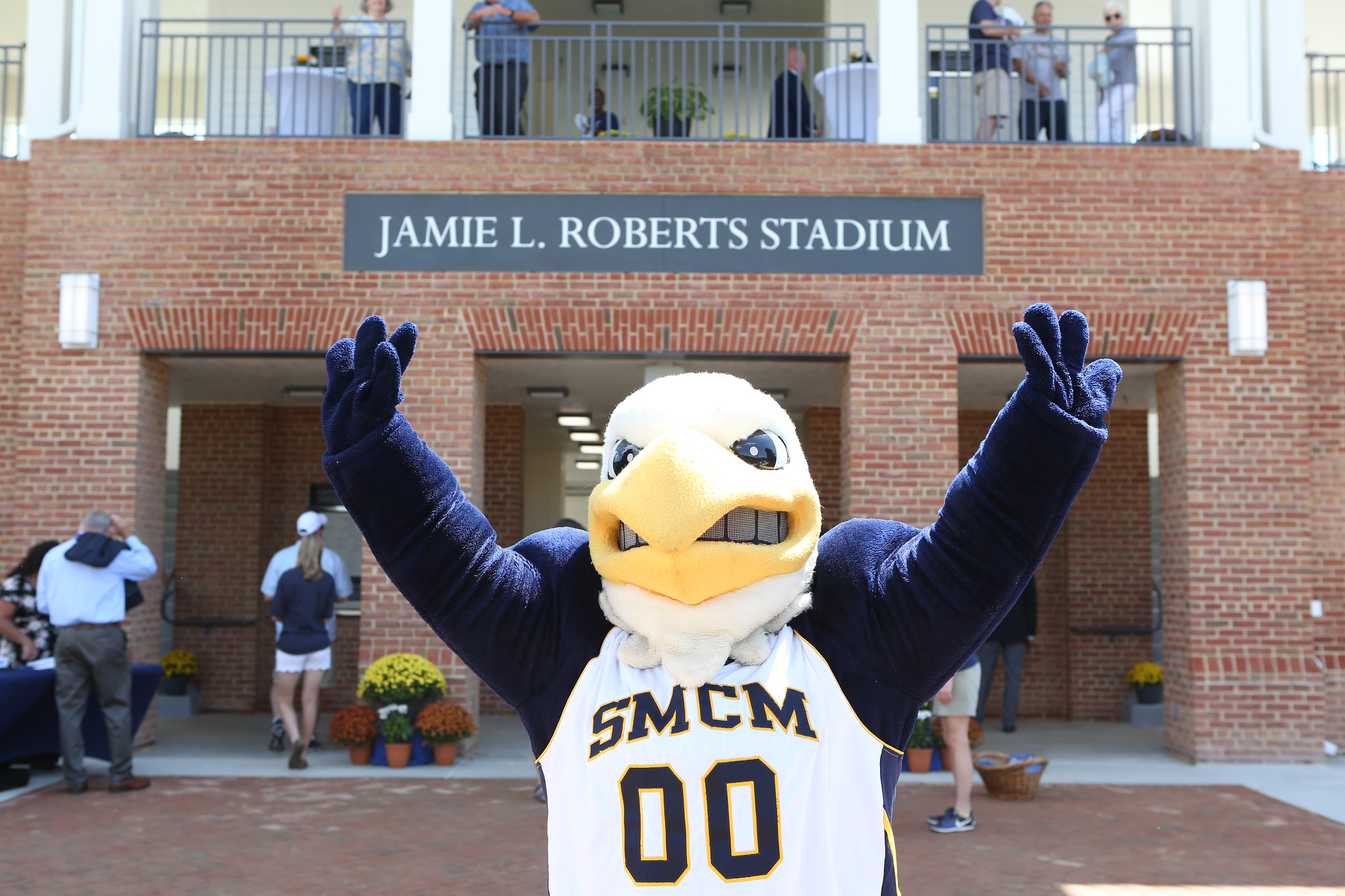 Our mascot, Solomon the Seahawk stands with it's arms raised in the air in front of Jamie L. Roberts Stadium sign.