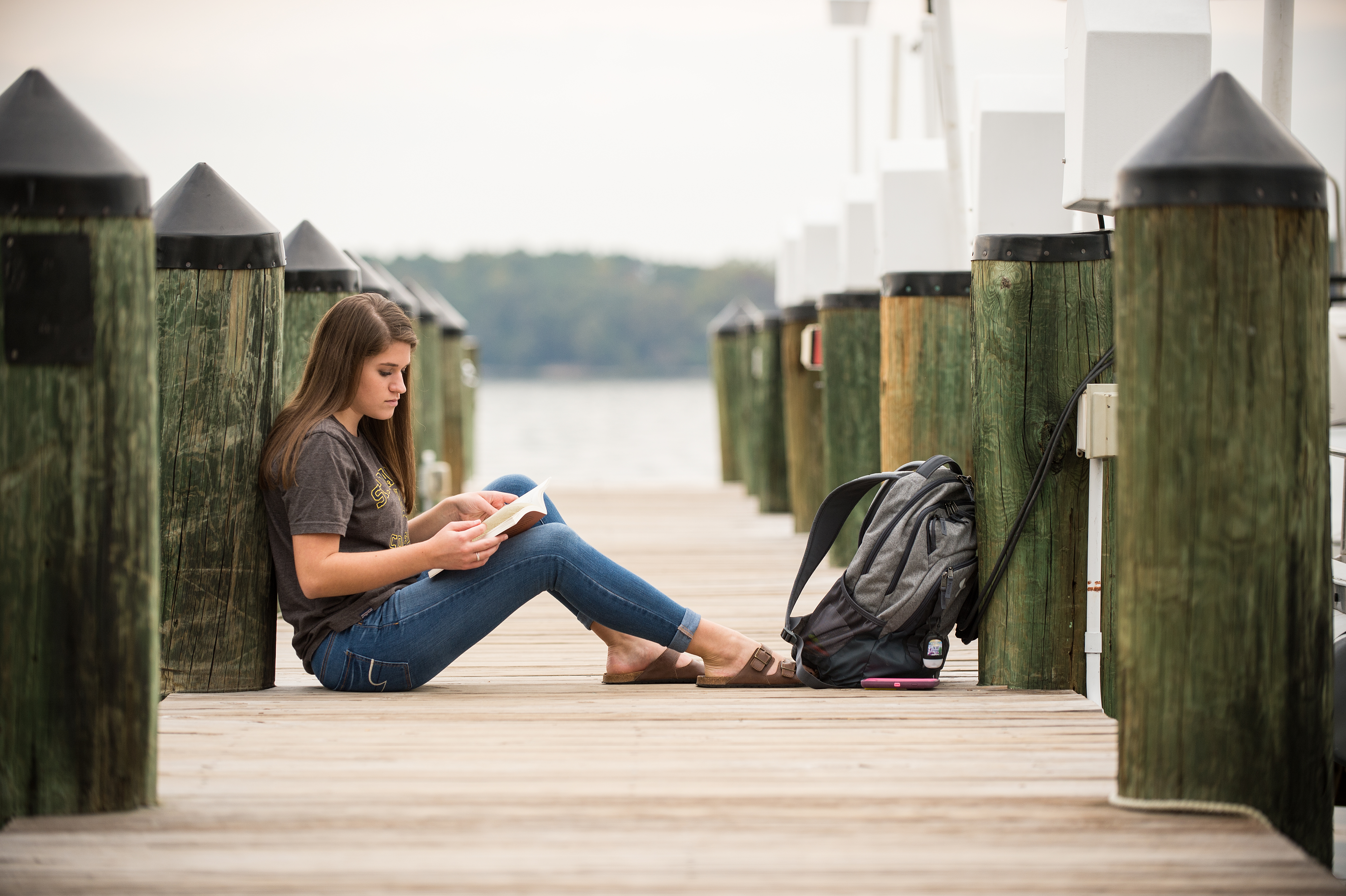Female Student reads a book on the dock by the St. Mary's River