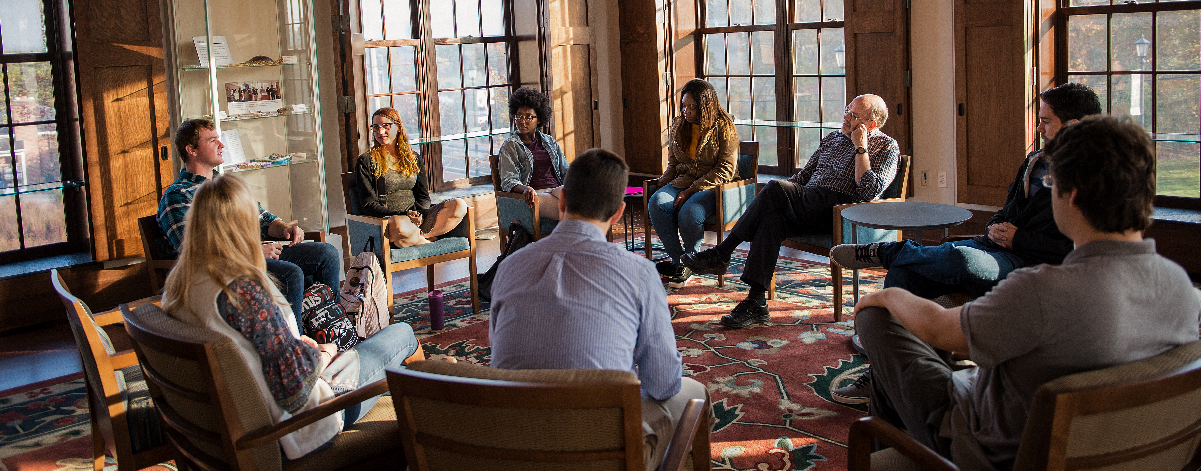 8 students and a professor sit in a circle in a group discussion in a room full of windows.