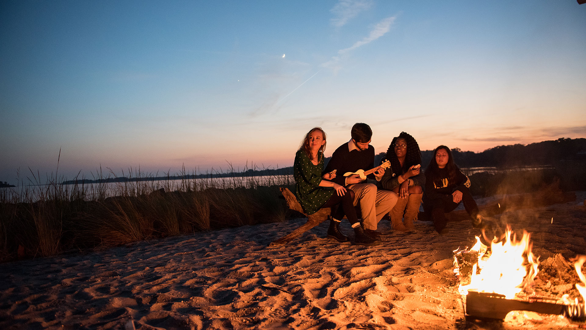 Group of 4 students site by a bonfire on the beach by St. Mary's river.
