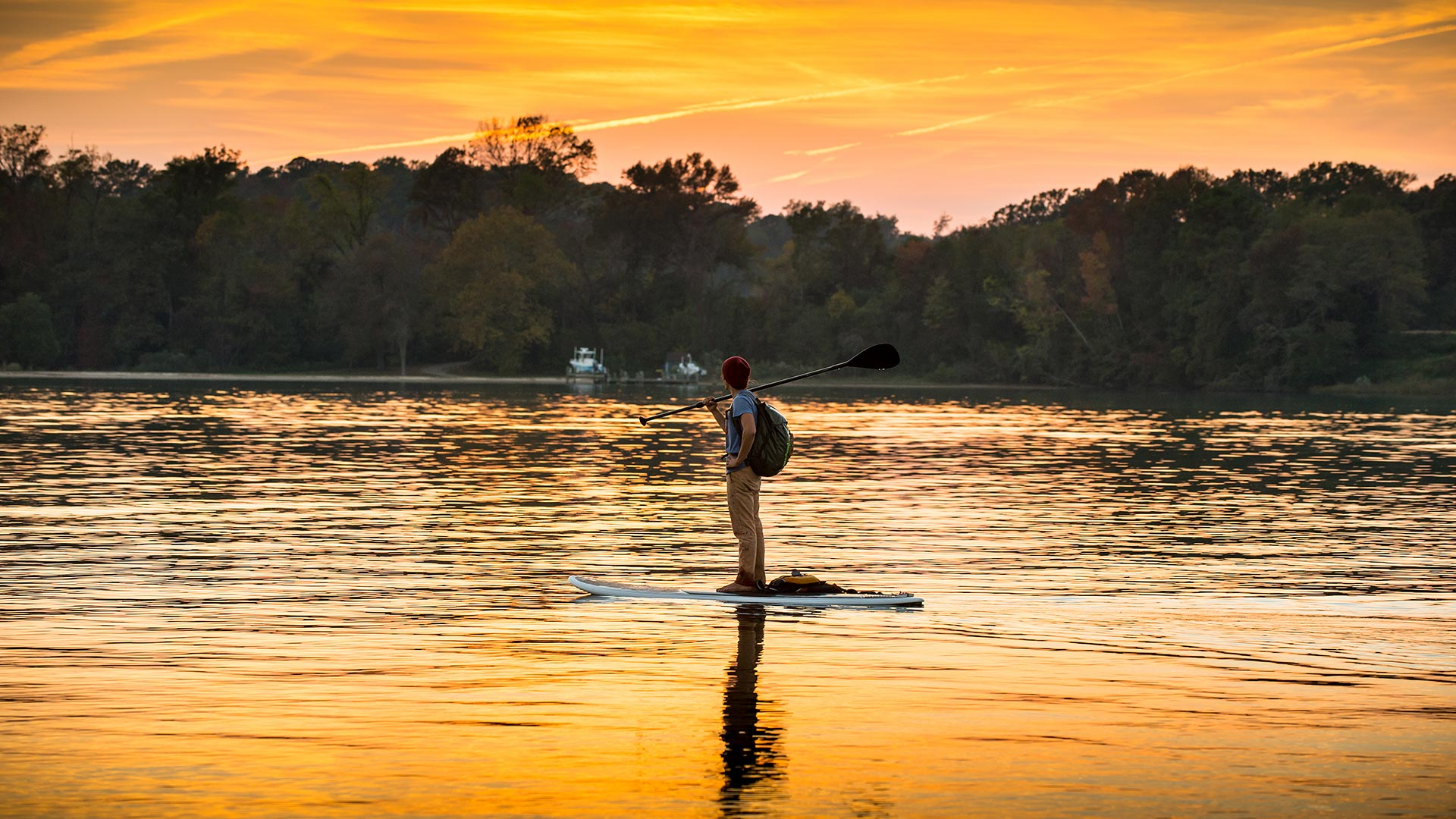 Male student with backpack on stands on a paddleboard admiring a beautiful yellow and orange sunset.