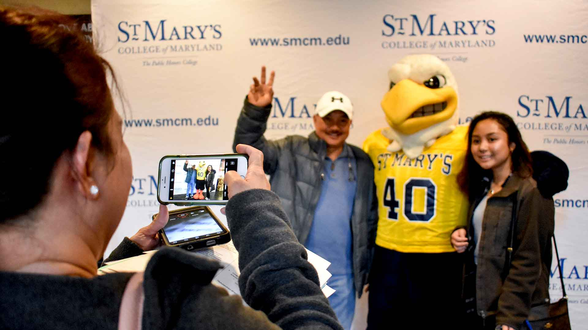 SMCM Admitted Students day photoshoot with Solomon the Seahawk and new female student and family members