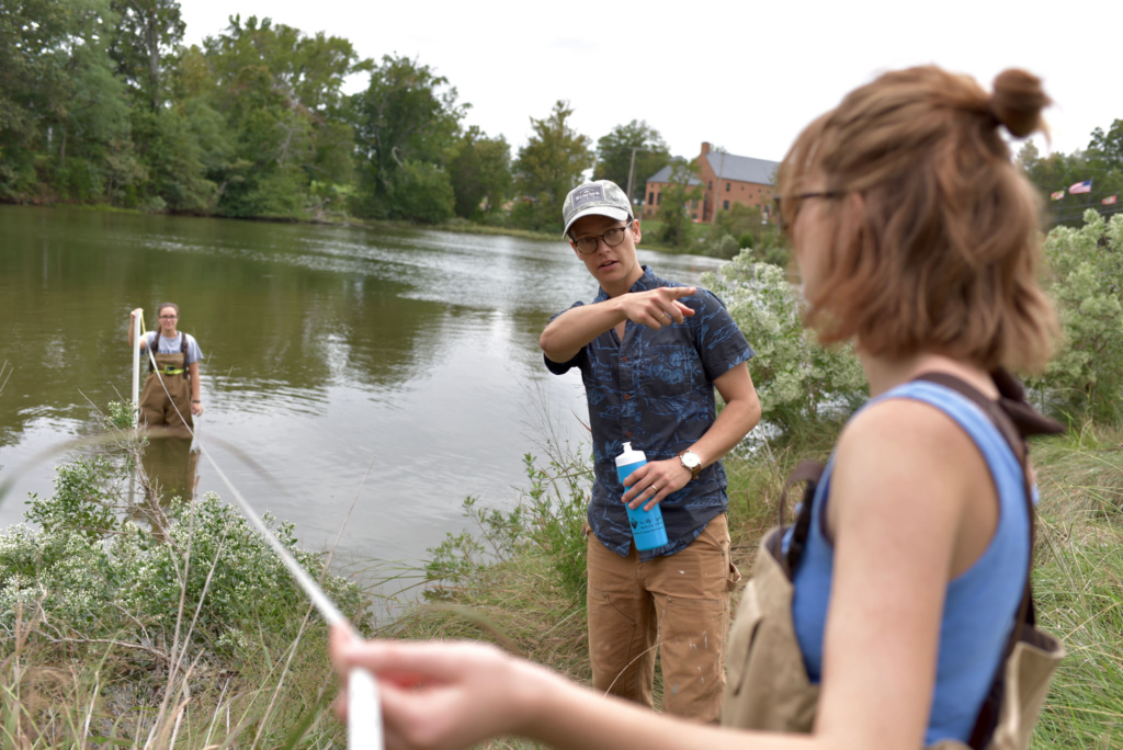 Three students perform a biology field exercise near the water